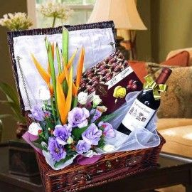 A Bottle of Red Wine with Chocolates and Flower Arrangement in a basket